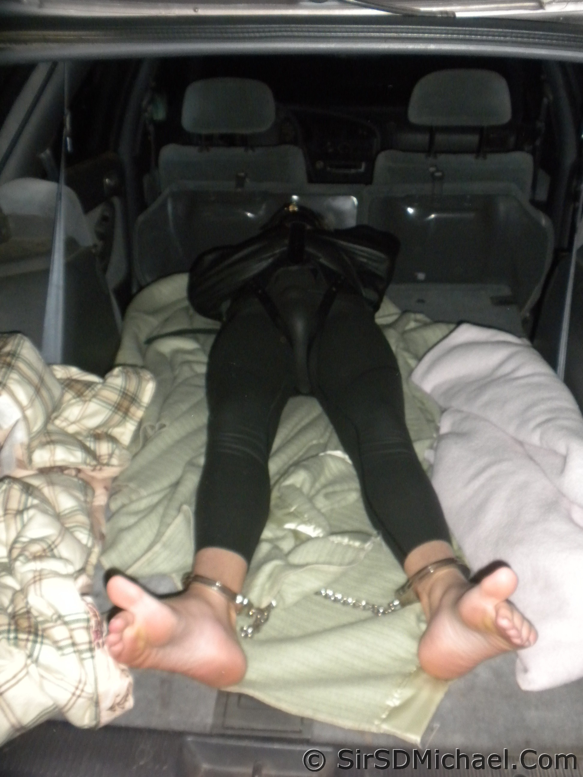 Bondage transport. Boy in a straitjacket, gagged, and in leg irons, being transported in my old station wagon.