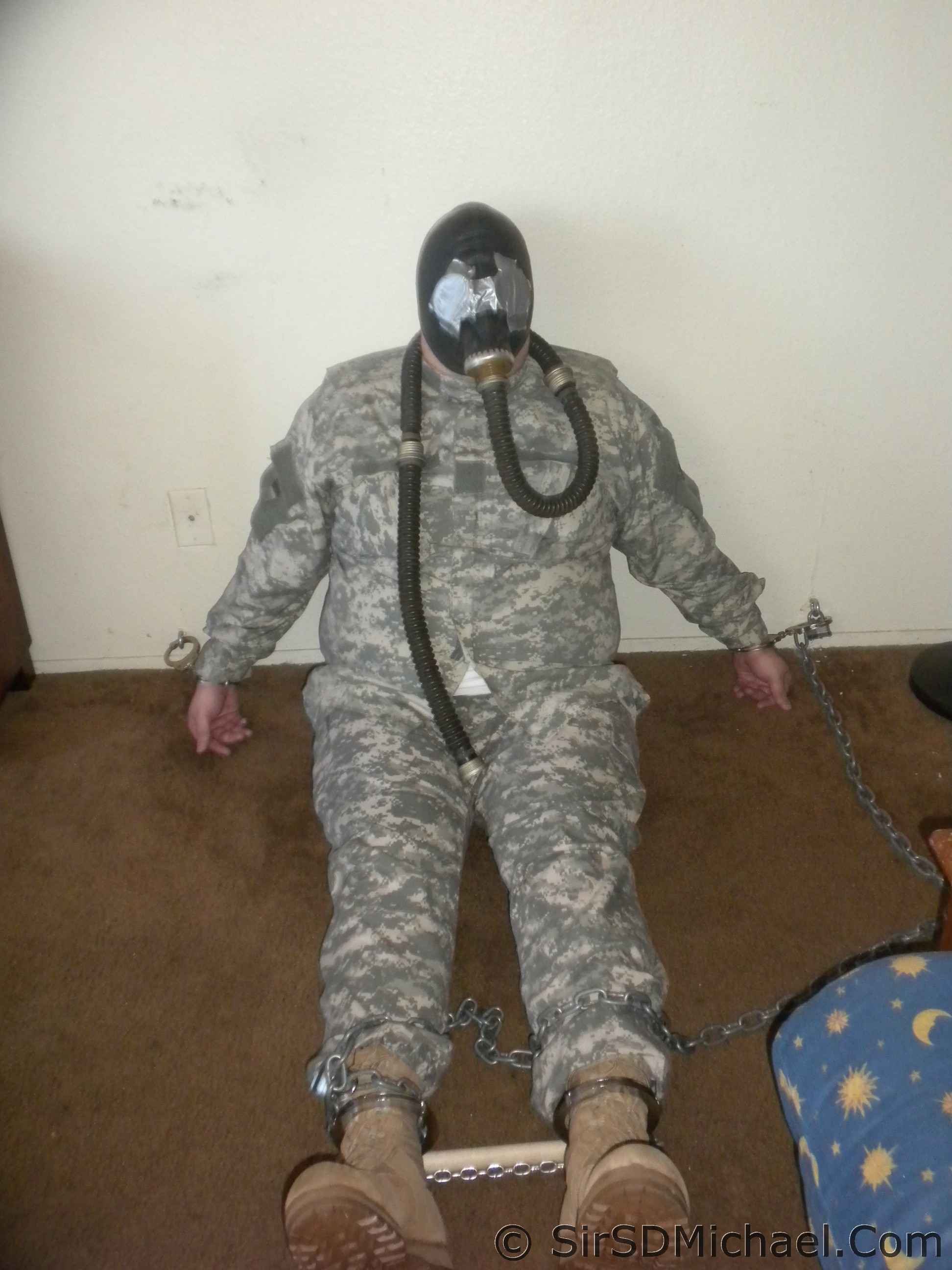 Gas Mask and ACU's - Boy is cuffed to the wall and blindfolded.