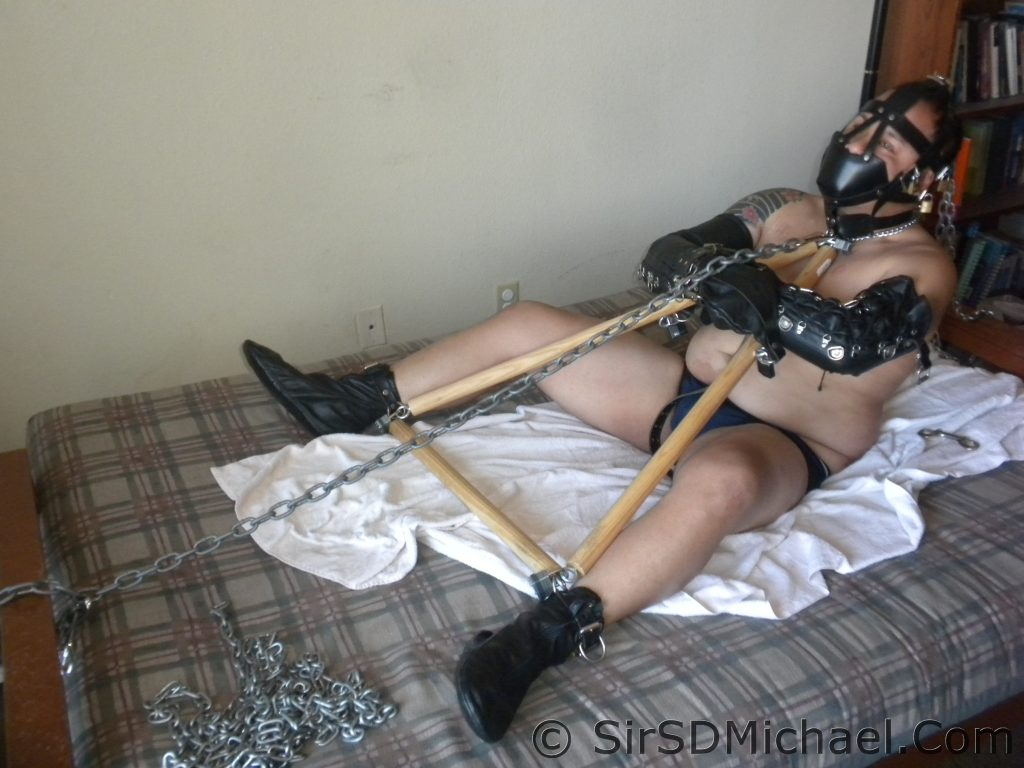 Chained to the bed at one end.