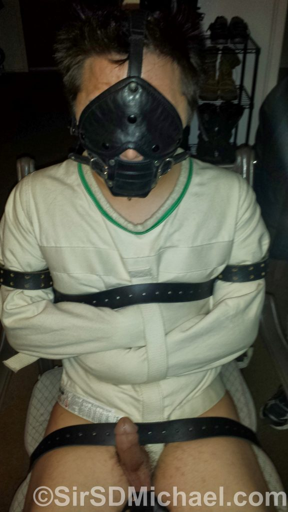 Boy tied with many bondage belts in use. Two to strap hold him to the chair and one as a strap on the straitjacket.