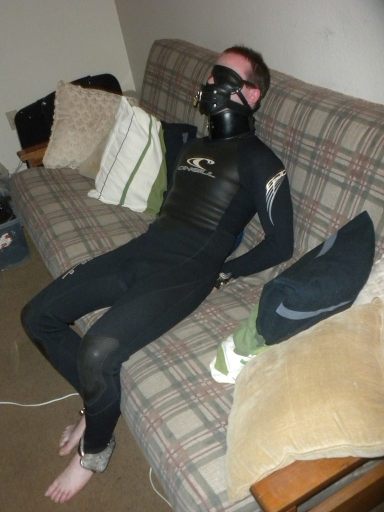 Bound boy in a wetsuit. Leg irons chained to handcuffs behind his back make it tough to get far.